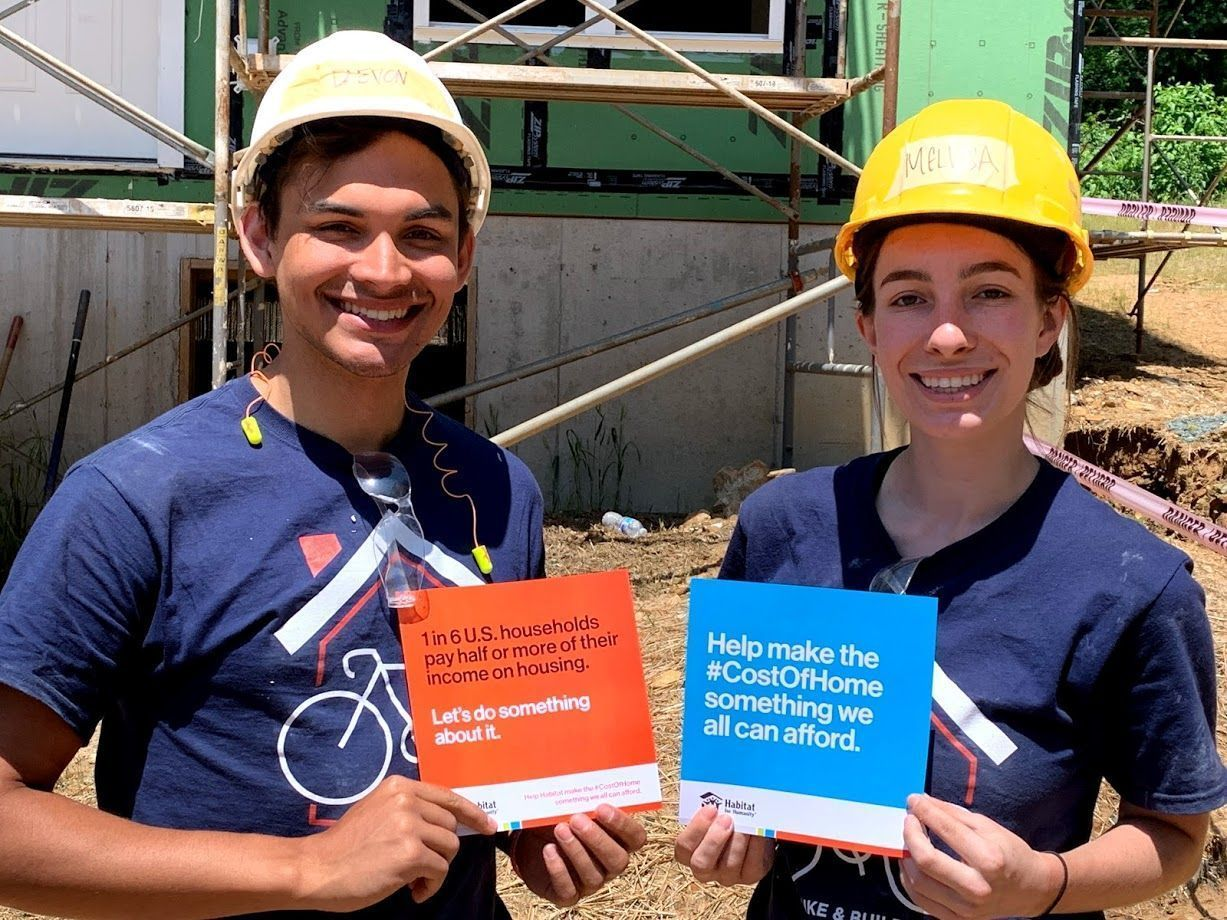 Man and woman smiling and holding Habitat for Humanity flyers.