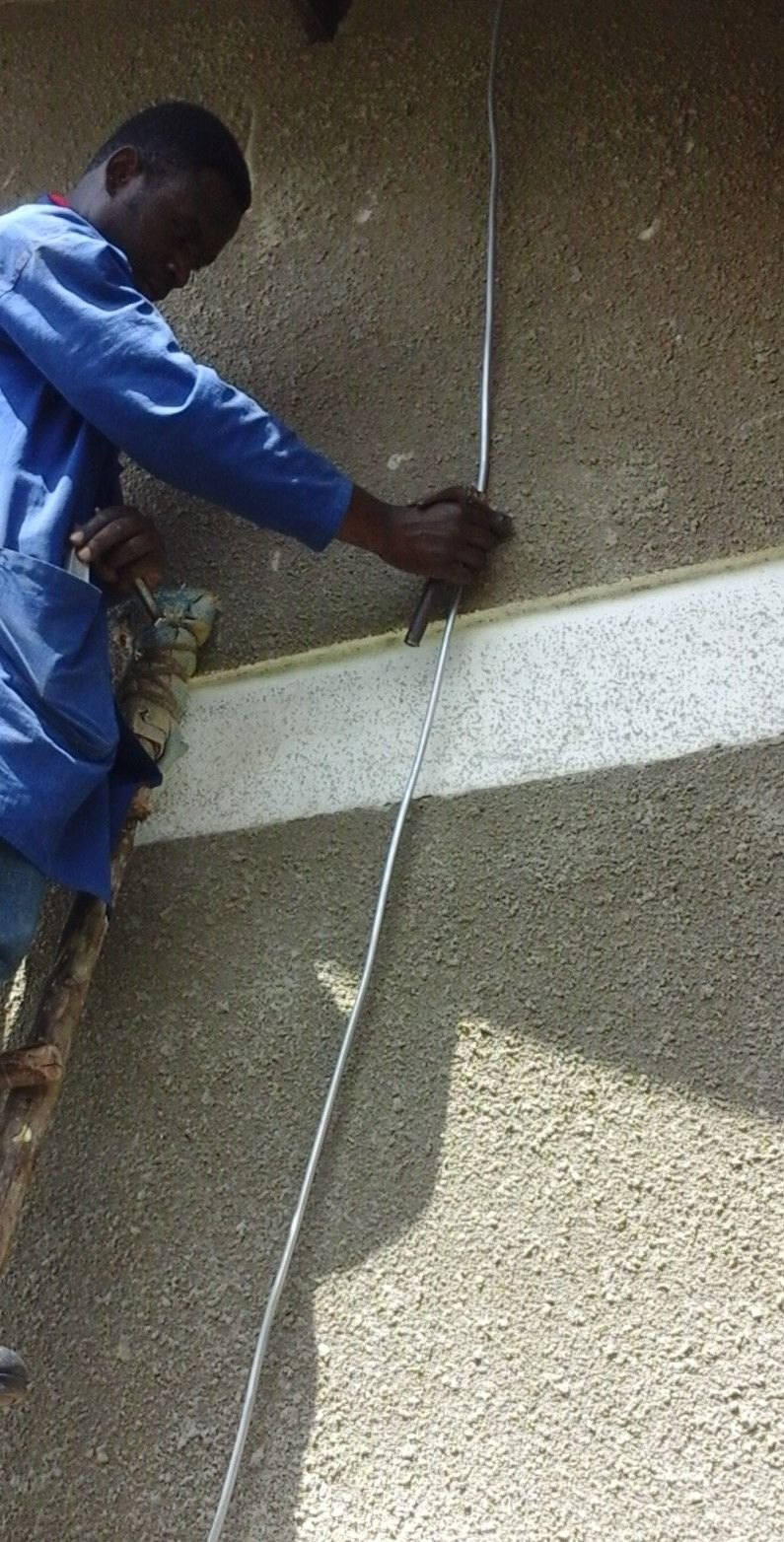 Installing down-conductors which carry lightning current from the lightning rods harmlessly to the earthing/grounding rings buried in trenches around each building