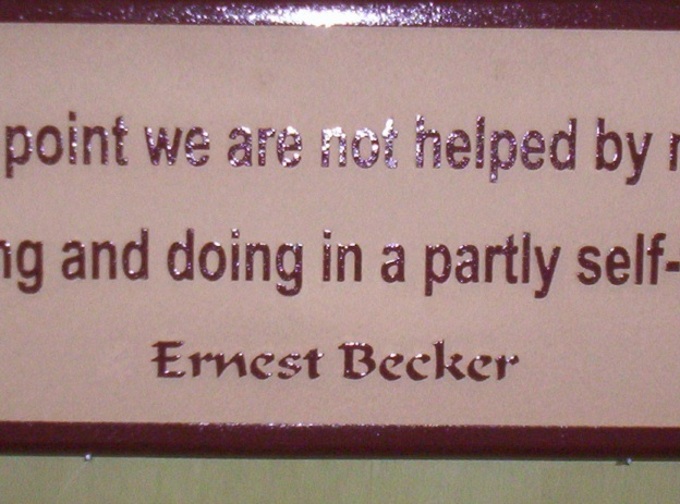 N23176 - Close-up of Carved Wall Plaque with Saying by Ernest Becker, Jewish-American cultural anthropologist and writer.