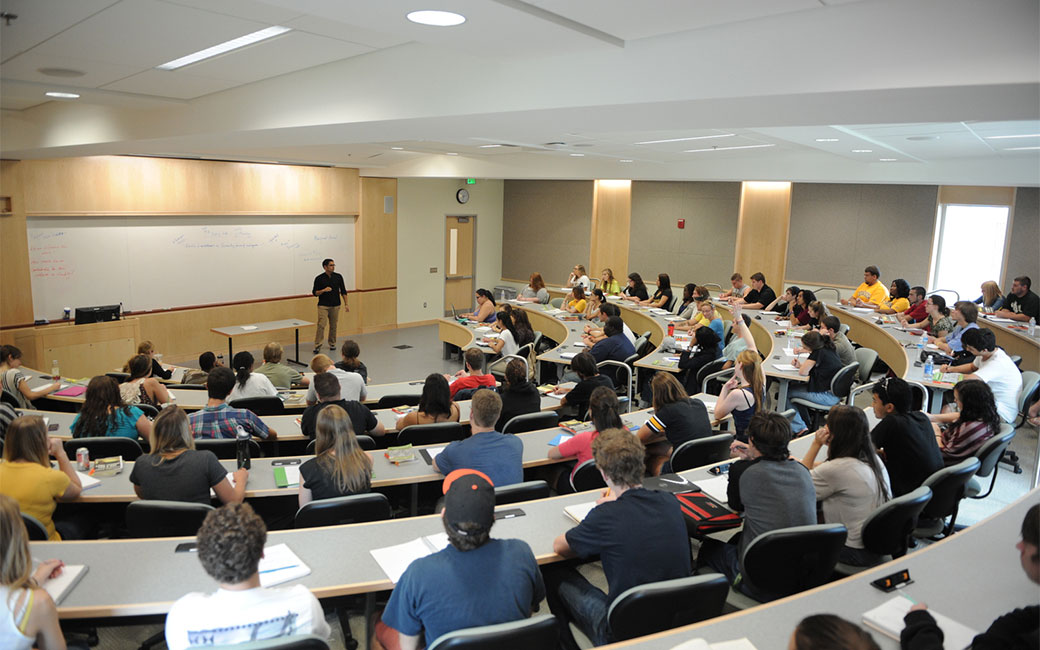 Large lecture hall of students sitting in rows in a semi circle with white board at front of class