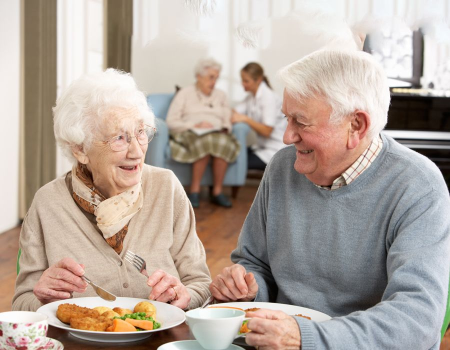 Female and male older adults sitting around a table and enjoying a meal, smiling at each other
