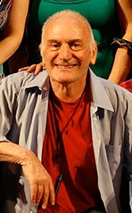 IKE SCHAMBELAN, A bald man with a big smile on his face. He is wearing a red t-shirt and a gray shirt over it. His arm is leaning on something to his right. He is facing the camera directly.