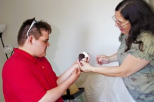 (Left) Shaine from one of our featured stories holds a hamster.  (Right) Shaine's staff is across from him and she is helping him to support teh animal in his hands