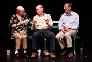 (L-R): J.M. McDonough (Man Three), Kenneith Kimmins (Man One) and John Little (Man Two) in Neil LaBute's CRIPPLES. Three friends sitting on a bench are dressed in business casual attire. They are having a conversation.