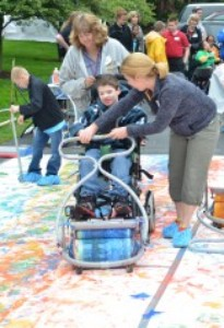 A young boy uses adaptive art equipment to transform his wheelchair into a painting tool.