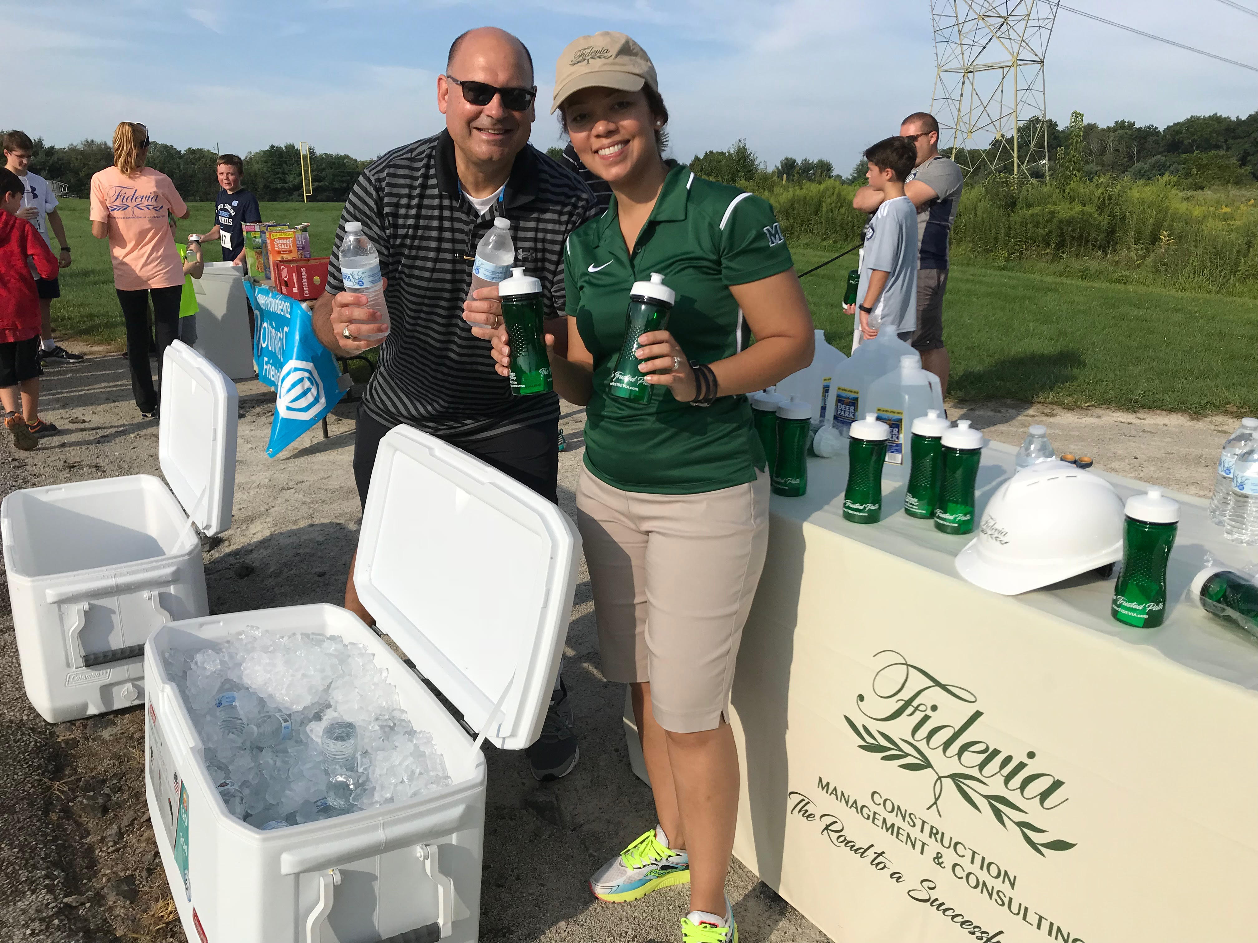 Fidevia Hands Out Water to Runners at 5K