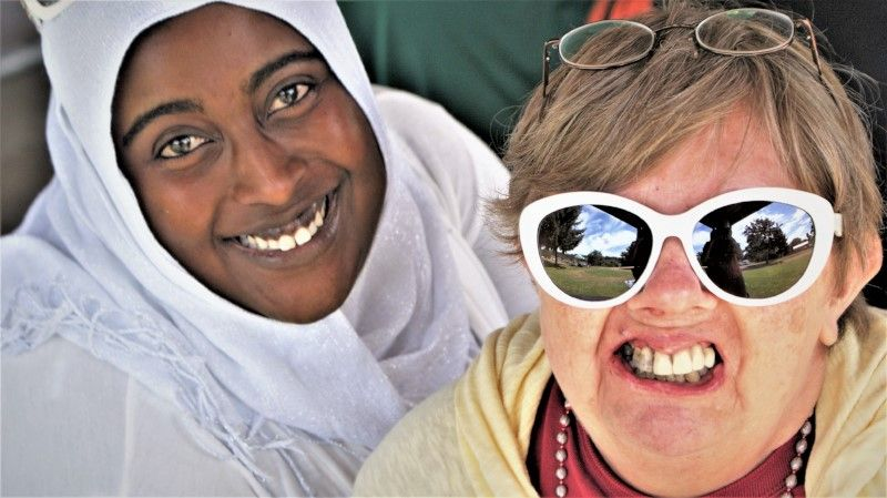 Close up of faces. (Left) African woman in white hijab smiling at camera . (Right) Woman supported by PSRS wearing big white sunglasses, with a big toothy smile