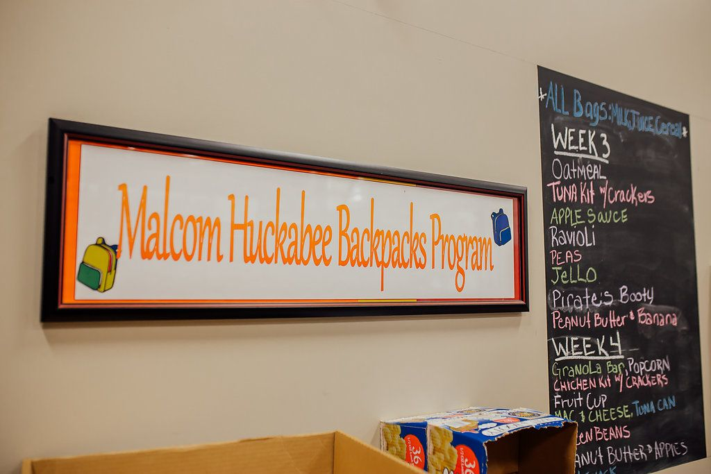 """Sign that reads, """"Malcom Huckabee Backpacks Program"""" with yellow and blue backpacks in the corner."""