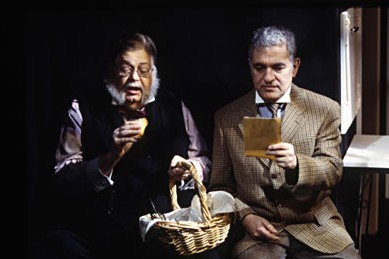 Jerry has a grey beard and is wearing a black vest with a plaid shirt, he's sitting on a chair in dim lighting, holding a basket while eating something. George is sitting next to Jerry in a lighter lighting while reading a paper.