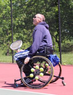 Man in wheelchair playing tennis