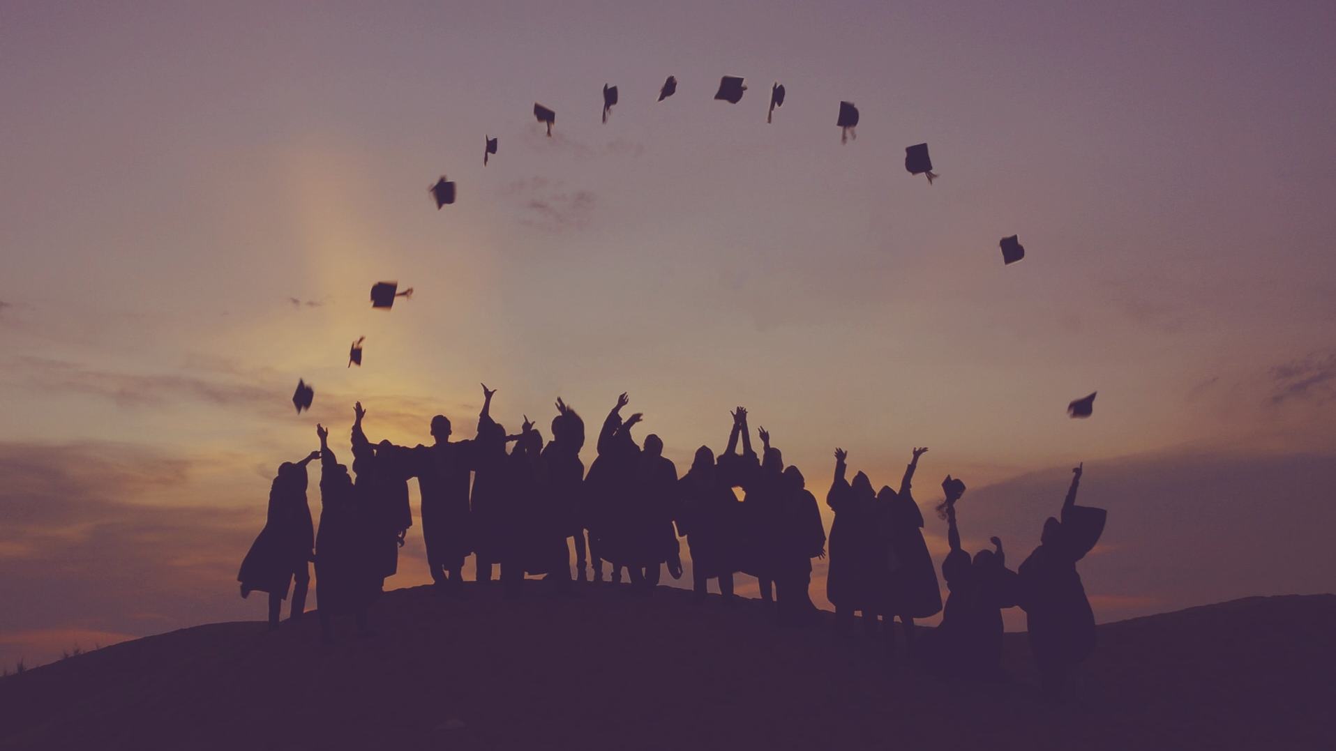 Silhouttes of group of people wearing graduation robes and tossing caps in air