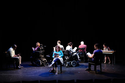 A dark scene with people who are both in wheelchairs and in regular chairs. They are all seating in in a circle and reading articles on different platforms, but they are all facing outward. One person is reading at the table in right corner of the room.
