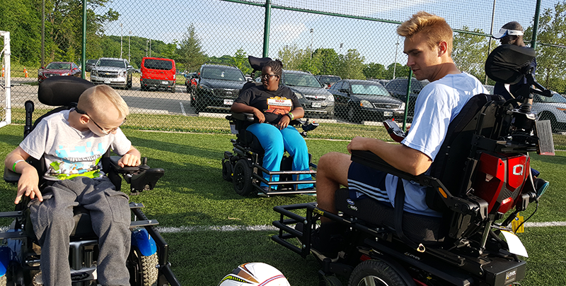 Photo of KC Sporting player in power wheelchair talking to young boy in power chair