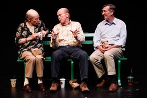 (L-R): J.M. McDonough (Man Three), Kenneith Kimmins (Man One) and John Little (Man Two) in Neil LaBute's CRIPPLES. Three friends sitting on a bench are dressed in business casual attire. They are having a conversation and they have coffee based drinks at