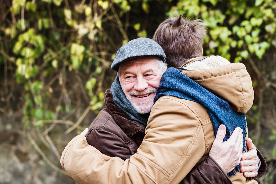 Older man smiling outside and hugging his adult son