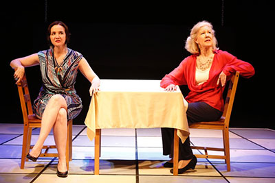 BETWEEN by John Guare (L to R): Pamela is wearing a multi-color dress sitting with her legs crossed. Melanie is wearing a red sweater, white blouse, black pants and seated across a table. They're not looking at one another.