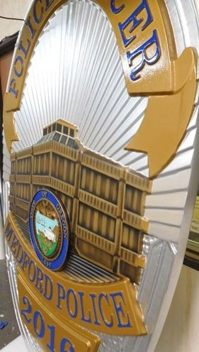 M7458 - Close-up of Metallic Silver and Gold Painted Carved  Wall Plaque featuring the badge of a Police Officer in Medford , Oregon.