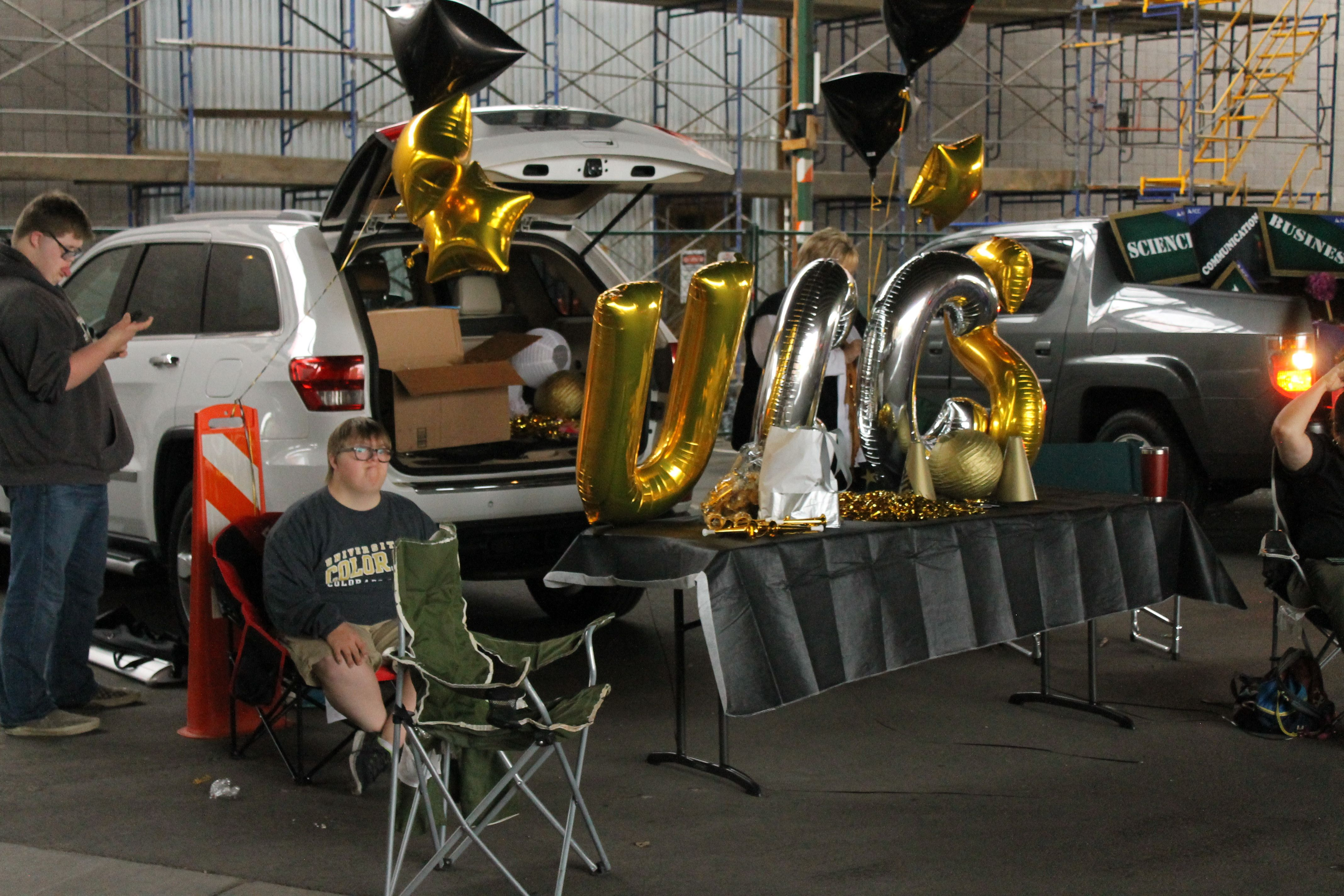 Man sits in sports chair next to table with large balloons reading UCCS