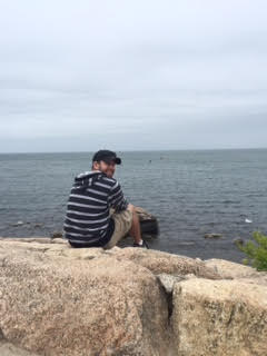 Photo of Brian Switzer on a rock overlooking the ocean