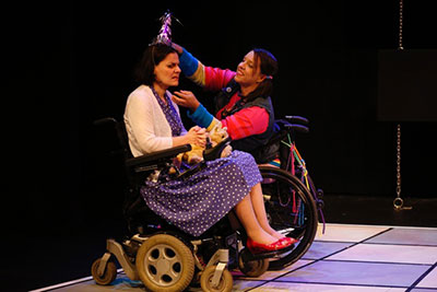 (L to R): Ann Marie is wearing a purple dress and white sweater. Jamie is wearing a multicolor outfit. They are in wheelchairs and Jamie is placing a party hat on Ann's head.